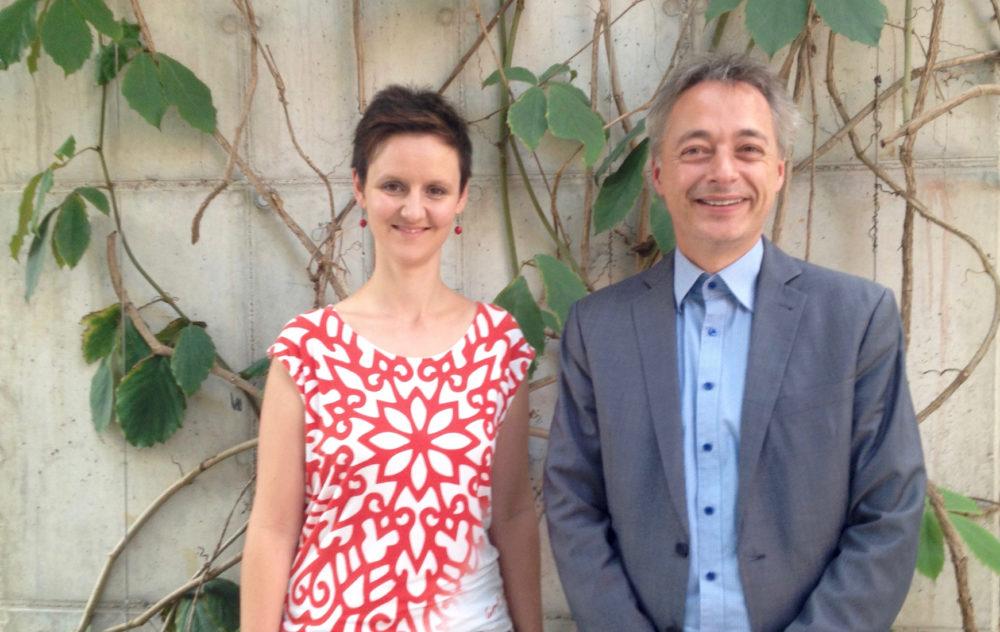 Eine junge Frau und ein Mann mittleren Alters vor einer bewachsenen Wand