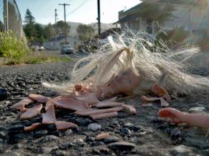 Stücke einer Barbie-Puppe auf einer Straße