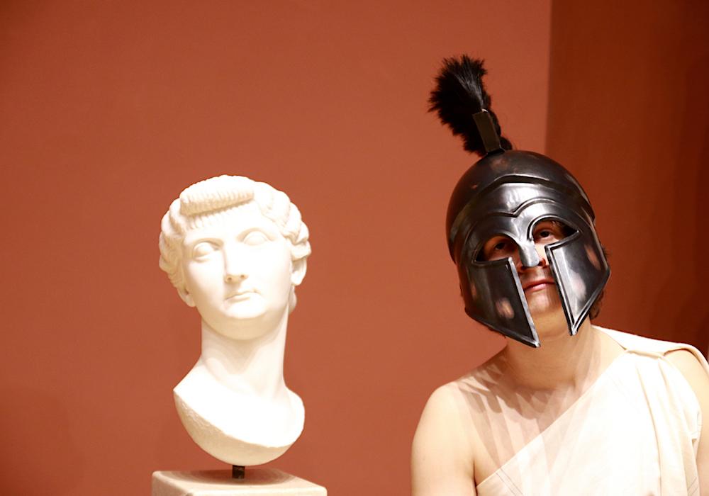 Ein junger Mann mit Helm steht rechts neben einer antiken Büste