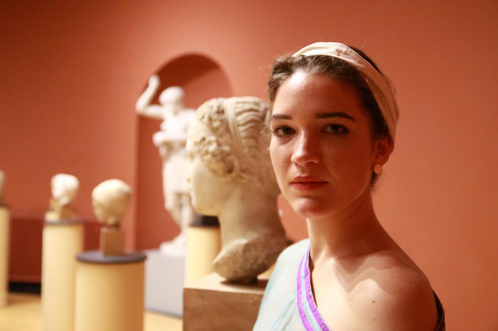 Eine junge Frau mit Kopfband, antike Büsten im Hintergrund