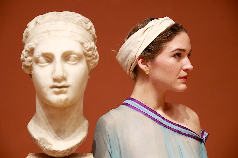 Eine junge Frau mit Kopfband steht rechts neben einer antiken Büste