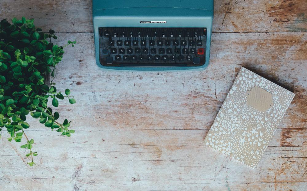 Eine blaue Schreibmaschine auf einem Holztisch
