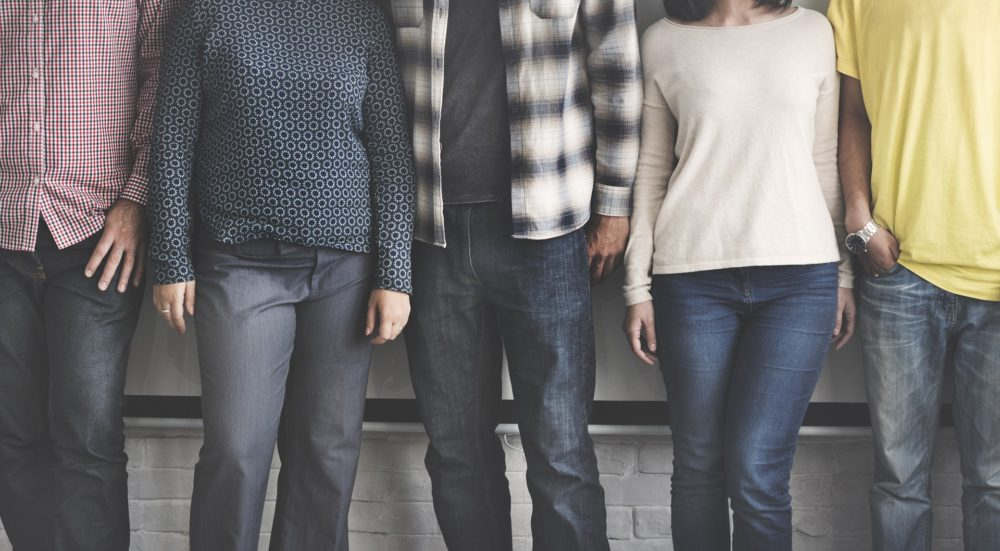 Fünf Leute, deren Köpfe man nicht sieht, stehen nebeneinander