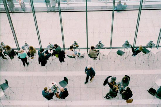 Viele Menschen an Tischen im Gespräch