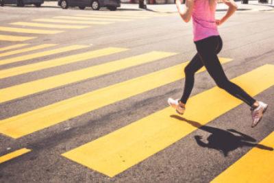Eine Frau joggt über einen Zebrastreifen