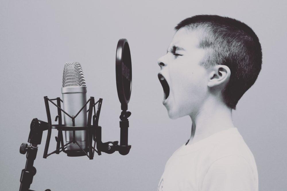 Ein Junge schreit in ein Mikrophon