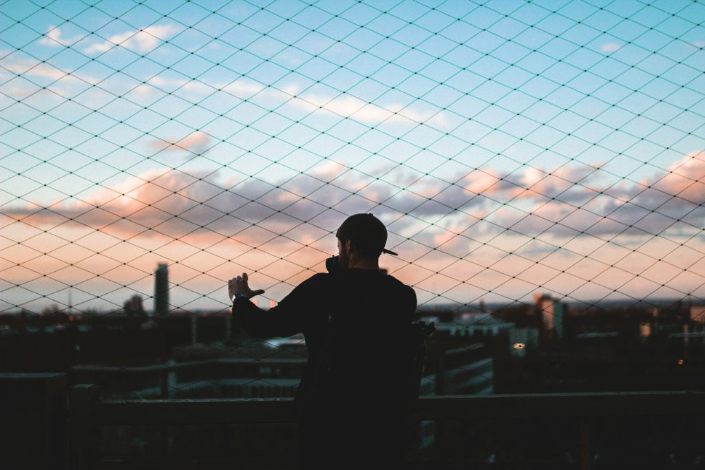 Ein Mann vor einem Zaun schaut auf Köln hinunter