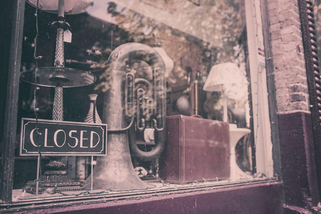 Eine Tuba und ein Lederkoffer im Schaufenster eines geschlossenen Geschäfts