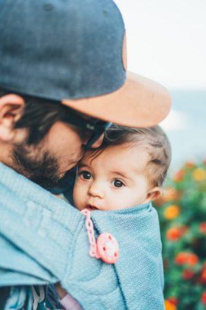 Ein Mann küsst das Kind in seinem Arm auf die Stirn