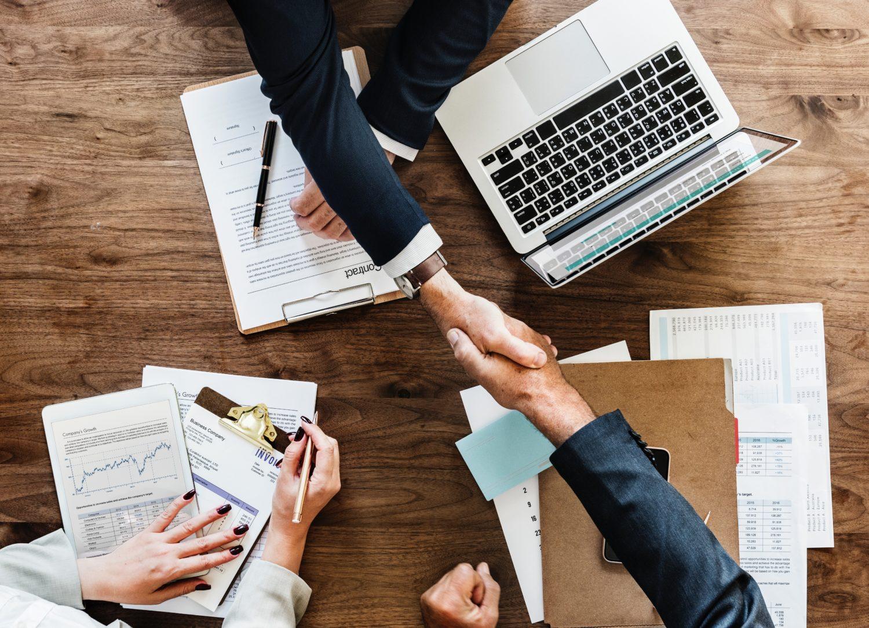 Drei Menschen an einem Tisch, zwei Männer geben sich über den Tisch hinweg die Hand