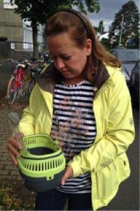 Eine Frau in einer Windjacke hält einen Brutkasten