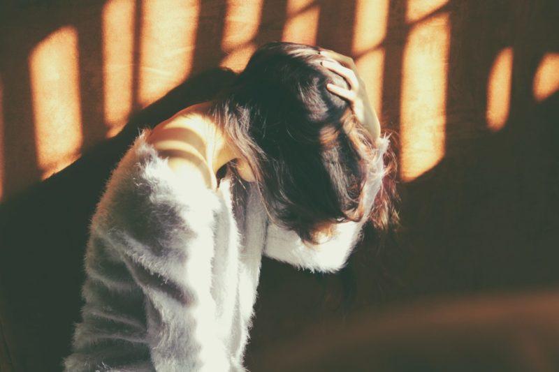 Eine Frau hält sich mit der linken Hand erschöpft den Kopf