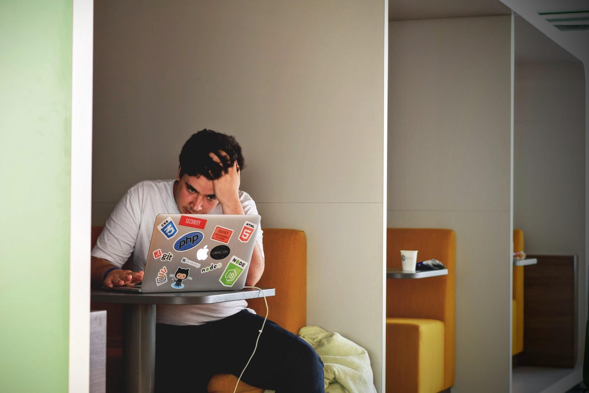 Ein junger Mann sitzt vor einem Laptop und hält sich angestrengt den Kopf