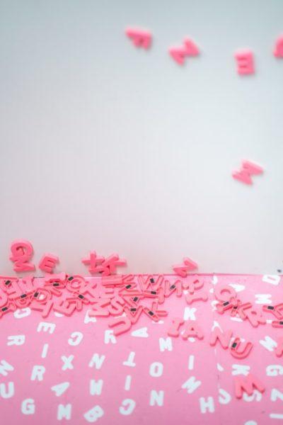 Pinke Plastikbuchstaben liegen auf dem Boden, ein paar kleben an einer Magnetwand