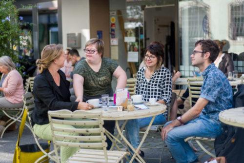 Vier Menschen mit und ohne Behinderung sitzen im Freien in einem Café.