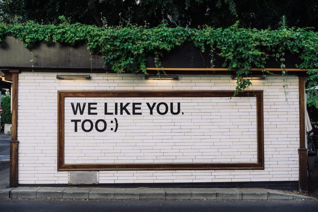 """Auf einer Mauer steht """"We like you, too"""" mit einem Emoticon am Ende"""